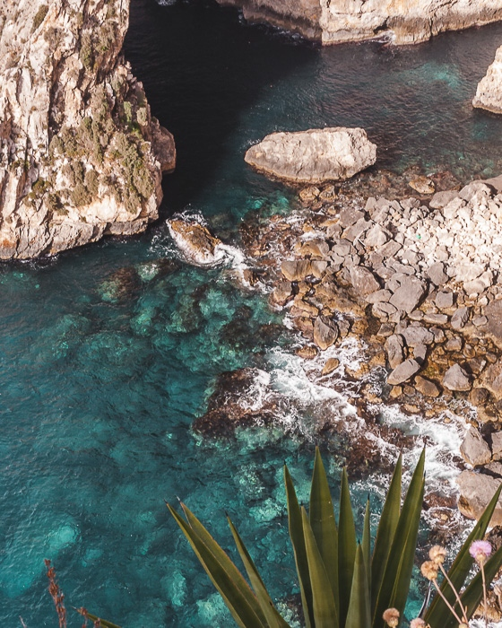 Malta travel guide crystal clear water of Blue Grotto by Dancing the Earth