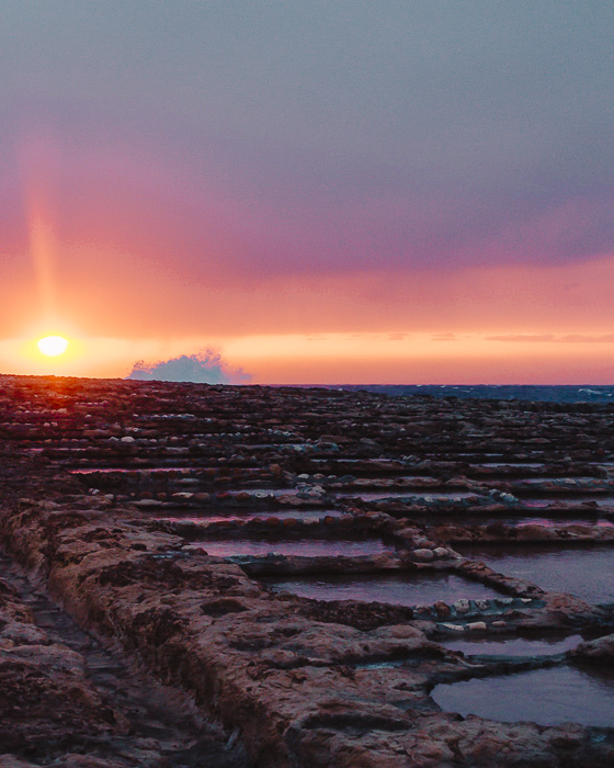 Malta travel guide Gozo island Ghajn Barrani salt pans at sunset with waves by Dancing the Earth
