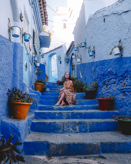Morocco travel guide Chefchaouen sitting on ocean-blue staircases by Dancing the Earth
