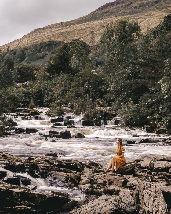 Falls of Dochart sitting on a rock in the river by Dancing the Earth
