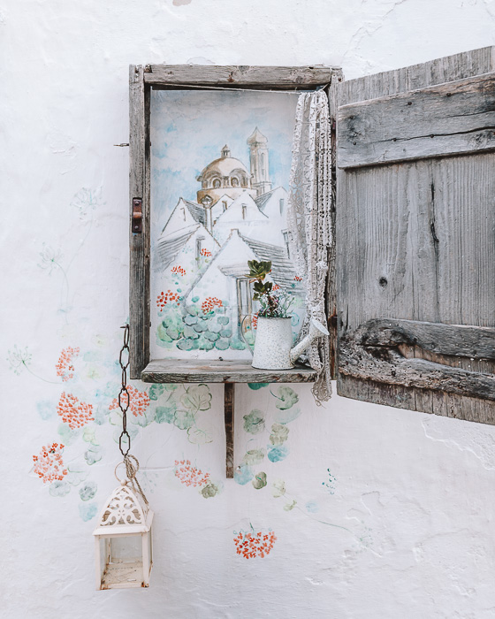 Locorotondo's wall drawing with a wooden window frame
